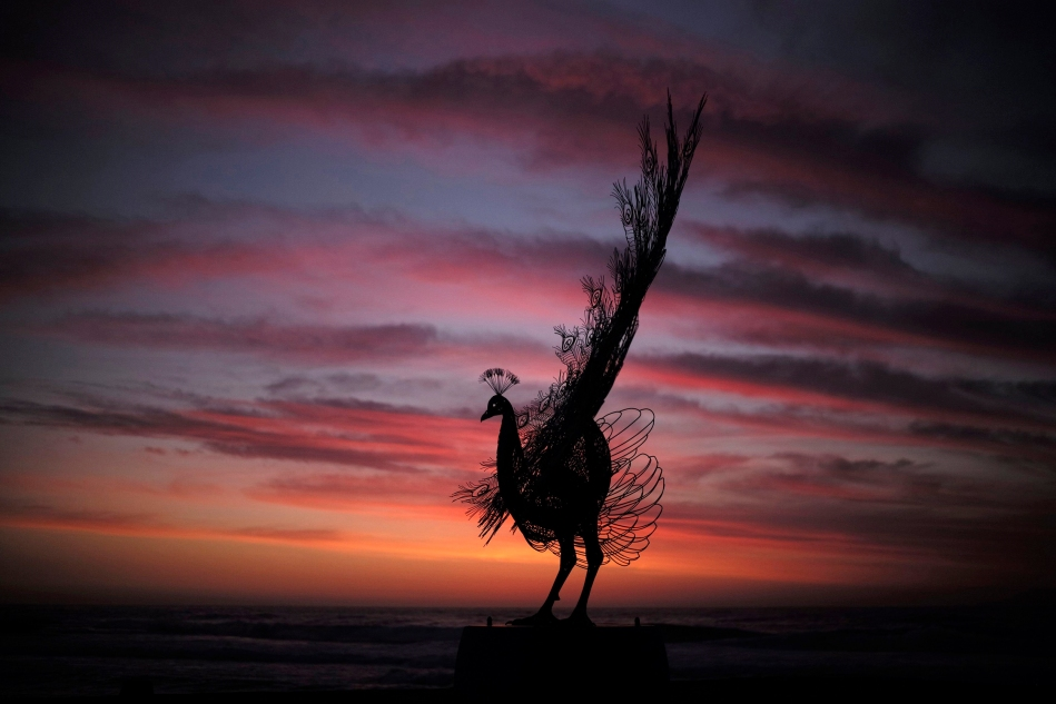 "Image: A sculpture by Byeong Doo-moon titled 'Our memory in your place' is shown before sunrise as part of the ""Sculpture by the Sea"" exhibition at Sydney's Tamarama Beach"